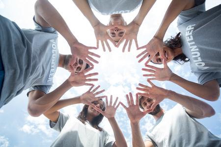 Foto de Low angle of happy volunteers playing with their hands - Imagen libre de derechos