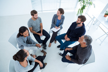 Foto de Upward angle view of a therapy group in session sitting in a circle in a bright room - Imagen libre de derechos