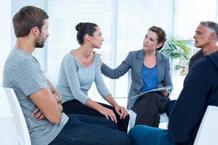 Photo pour Concerned woman comforting another in rehab group at a therapy session - image libre de droit