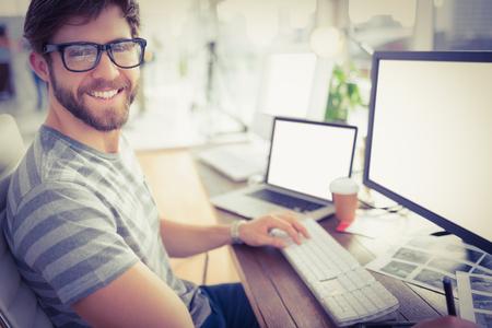 Foto de Portrait of a casual young businessman using computer in office - Imagen libre de derechos