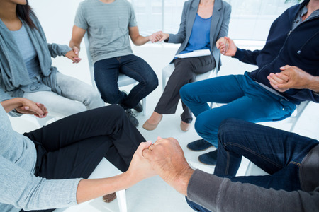 Photo pour Group therapy in session sitting in a circle in a bright room - image libre de droit