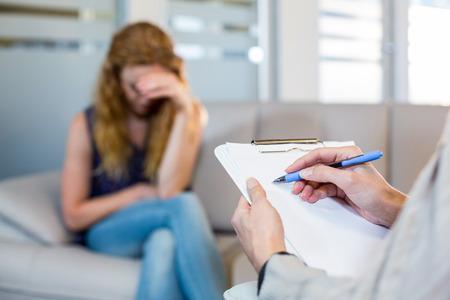 Foto de Psychologist talking with her depressed patient and taking notes in the office - Imagen libre de derechos