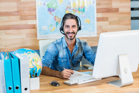 Photo for Smiling travel agent looking at camera in the office - Royalty Free Image