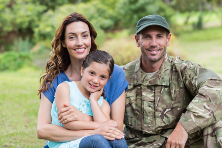 Foto de Handsome soldier reunited with family on a sunny day - Imagen libre de derechos