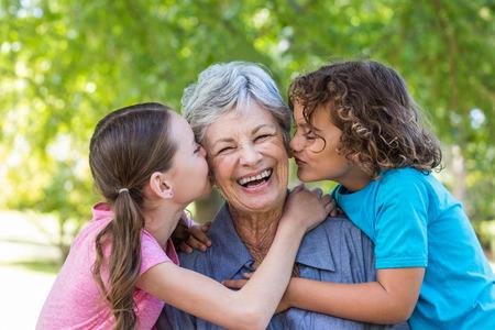 Foto de Extended family smiling and kissing in a park on a sunny day - Imagen libre de derechos