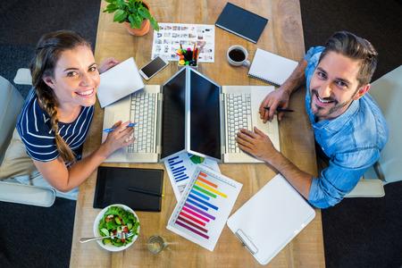 Photo pour Smiling partners working at desk using laptop in the office - image libre de droit