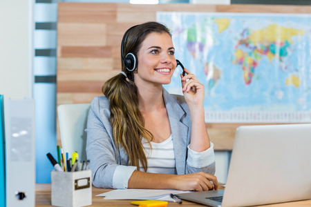 Photo for Pretty travel agent speaking to customer in the office - Royalty Free Image