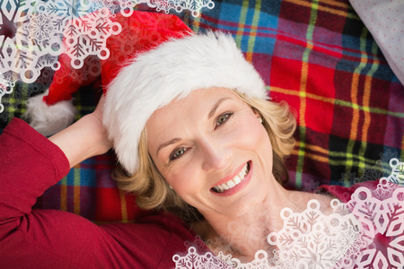 Festive blonde smiling on blanket against snowflake frame