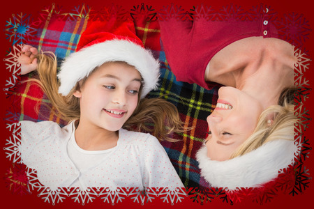 Festive mother and daughter smiling on blanket against snowflake frame