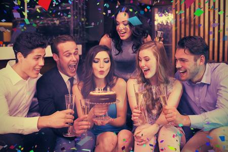 Foto de Attractive friends celebrating a birthday against flying colours - Imagen libre de derechos