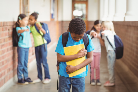 Photo pour Sad pupil being bullied by classmates at corridor in school - image libre de droit