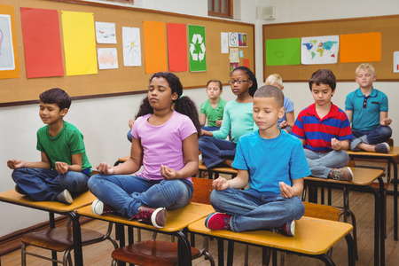 Photo for Pupils meditating on classroom desks at the elementary school - Royalty Free Image