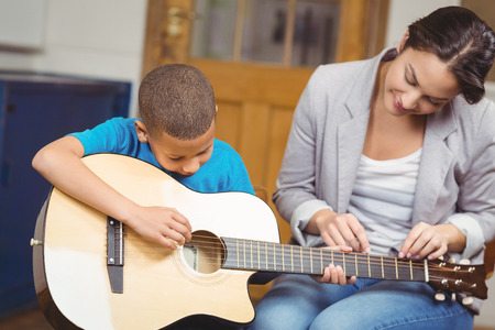 Foto de Pretty teacher giving guitar lessons to pupil  in a classroom - Imagen libre de derechos