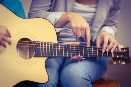 Photo for Teacher giving guitar lessons to pupil in a classroom - Royalty Free Image
