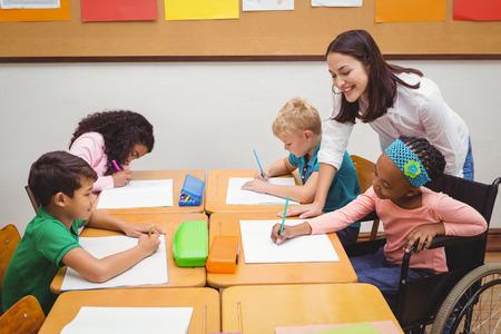 Foto de Happy teacher helping her students at the elementary school - Imagen libre de derechos