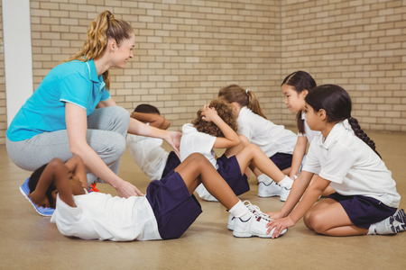 Photo pour Students helping other students exercise at the elementary school - image libre de droit