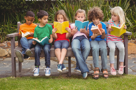 Photo pour Children reading from books together while sitting down - image libre de droit