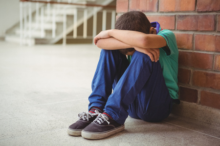 Foto de Upset lonely child sitting by himself on the elementary school grounds - Imagen libre de derechos