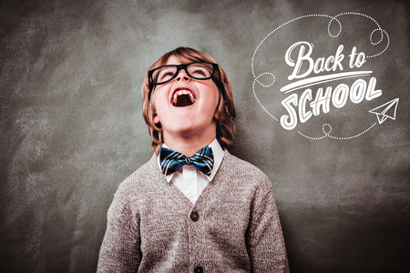 Photo pour back to school against boy laughing in front of blackboard - image libre de droit