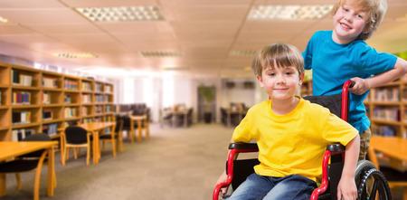 Foto de Happy boy pushing friend on wheelchair against view of library - Imagen libre de derechos