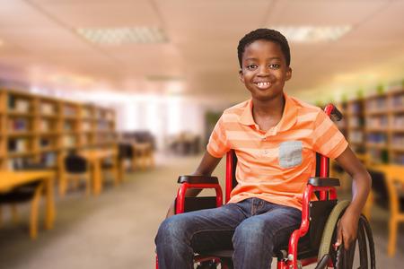 Foto de Portrait of boy sitting in wheelchair at library against view of library - Imagen libre de derechos