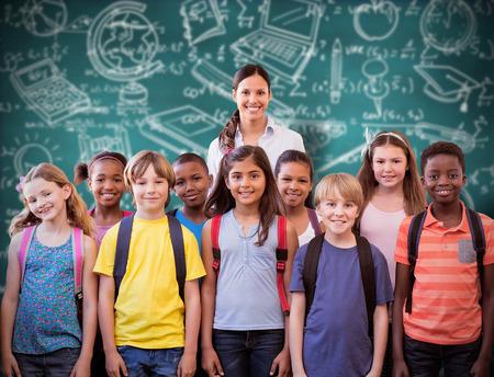 Foto de Cute pupils smiling at camera in the hall  against green chalkboard - Imagen libre de derechos