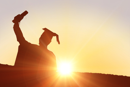 Silhouette of graduate against sun shining