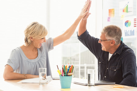 Happy business team doing a high-five together in the office