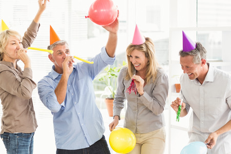 Laughing casual business people celebrating birthday in the office