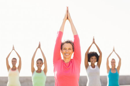 Photo for Portrait of smiling sporty woman doing yoga in yoga class in parkland - Royalty Free Image