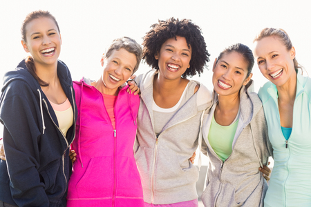 Photo for Portrait of laughing sporty women with arms around each other in parkland - Royalty Free Image