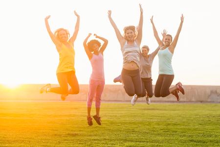 Photo pour Portrait of happy sporty women jumping during fitness class in parkland - image libre de droit
