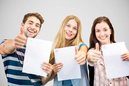 Foto de Students holding up exam and doing thumbs up against grey vignette - Imagen libre de derechos