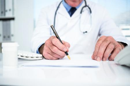 Foto de Midsection of doctor writing on paper at clinic - Imagen libre de derechos