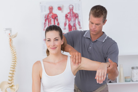 Photo for Doctor stretching a young woman arm in medical office - Royalty Free Image