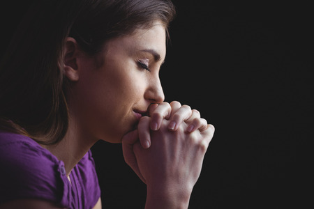 Photo pour Woman praying with hands together on black background - image libre de droit