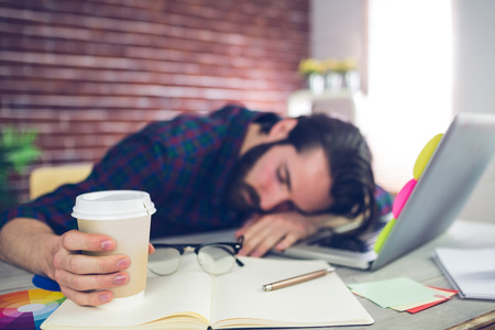 Photo pour Tired creative editor holding disposable cup while sleeping on office desk - image libre de droit