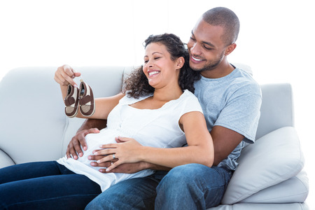 Cheerful young couple with baby shoes sitting on sofa at home