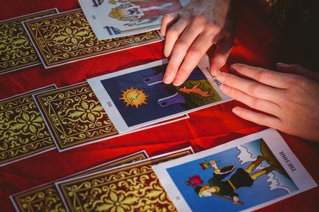 Photo pour Fortune teller using tarot cards on red table - image libre de droit