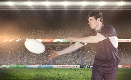 Rugby player doing a side pass against rugby fans in arena