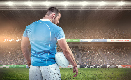 Rugby player standing with ball against rugby fans in arena