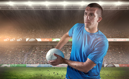 Rugby player looking away while holding ball against rugby fans in arena