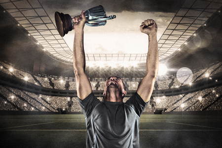 Foto de Happy rugby player holding trophy against large football stadium with lights - Imagen libre de derechos