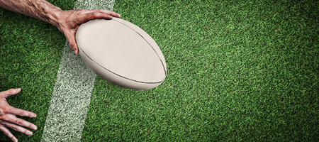 Cropped image of a man holding rugby ball against pitch with line