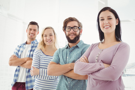Photo for Portrait of smiling business people standing in row with arms crossed at office - Royalty Free Image