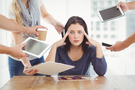 Photo pour Businesswoman having headache while sitting at desk - image libre de droit