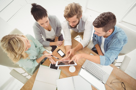 Photo pour Overhead view of business people with digital tablet while sitting at desk - image libre de droit
