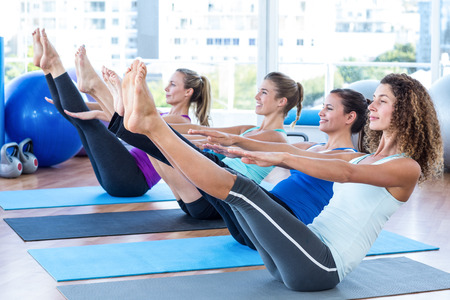 Foto de Fit women in fitness studio doing boat pose on exercise mat - Imagen libre de derechos