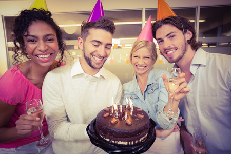 Photo pour Portrait of smiling business people with birthday cake enjoying the party in creative office - image libre de droit