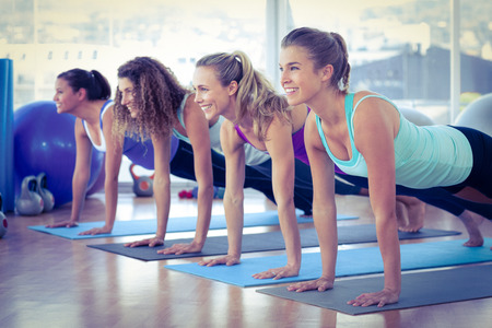 Women smiling while doing plank pose on exercise mat in fitness center